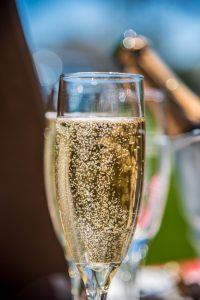 Champagne glass macro closeup with bubbles at outdoor wedding
